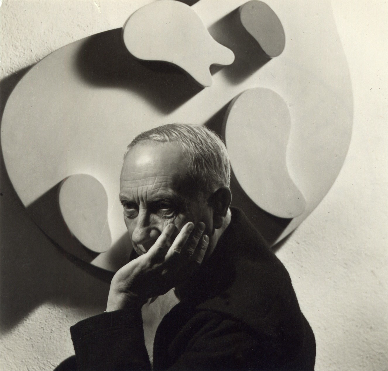Hans Arp in front of one of his reliefs, Basel, 1946/1947 (Photograph: Atelier Eidenbenz)