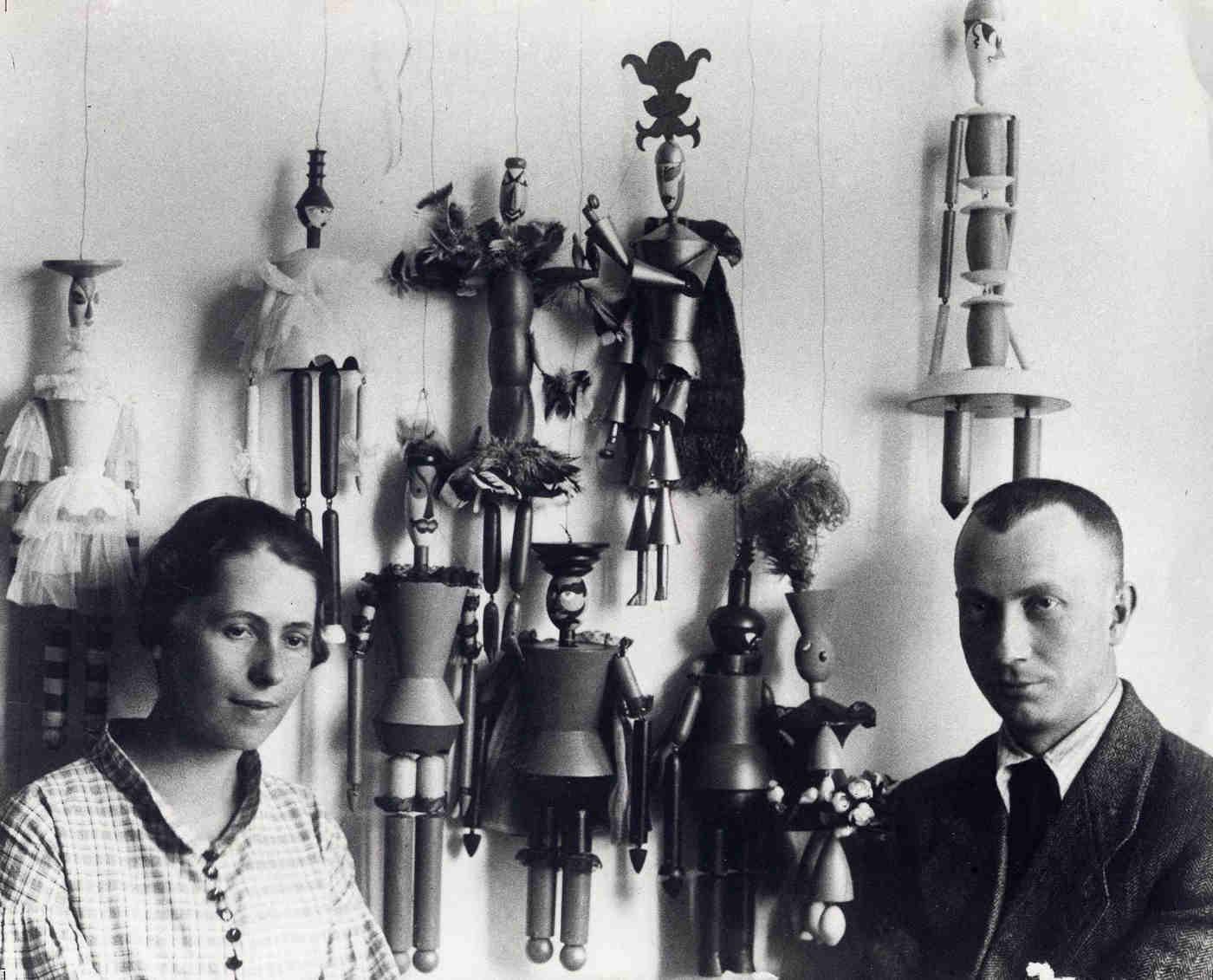 """Sophie Taeuber und Hans Arp vor den Marionetten für das Stück """"König Hirsch"""", Zürich 1918 (Fotograf: Ernst Linck)"""